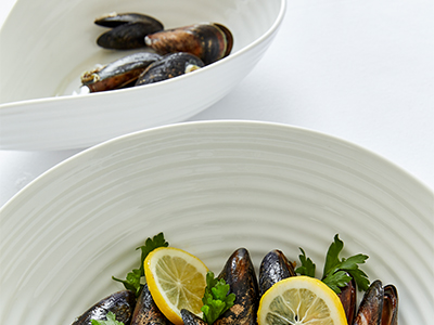 Beautiful, white Sophie Conran plates and bowls serving seafood